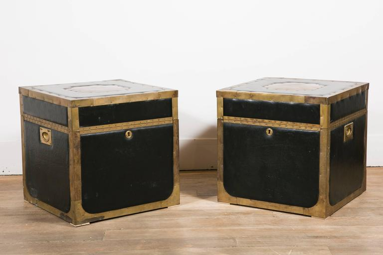 A pair of trunk tables. Black leather and brass edges.  Keys in working condition. Two brass handles.  England, 1960s.