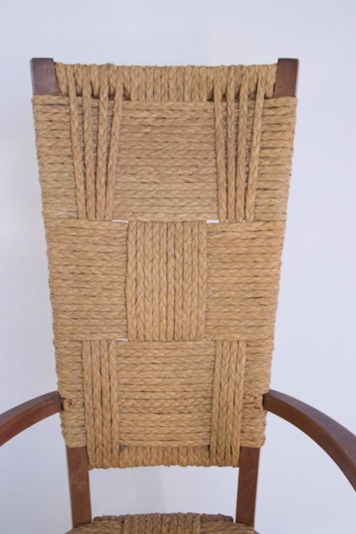 Audoux-Minet, suite of four armchairs, Rattan and wood,  circa 1970, France.  Measures: Height 110 cm, seat height 45 cm, width 56 cm, depth 40 cm.