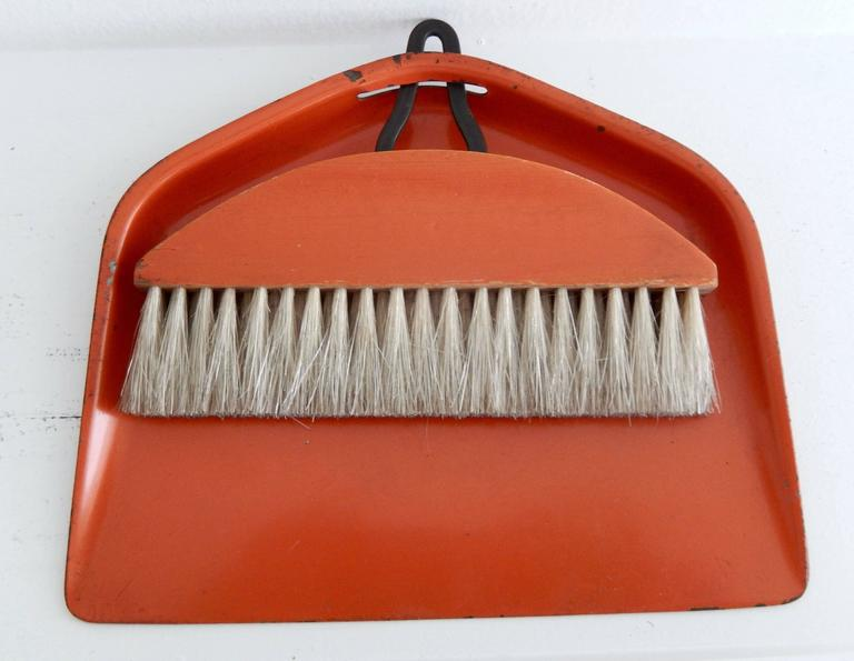 A burnt orange enameled sheet metal and horsehair brush and tray by the Bauhaus artist and Industrial designer Marianne Brandt (1893-1983). A functional, simple design exemplifying the best of Bauhaus metalwork. A fine example of pre-war modern