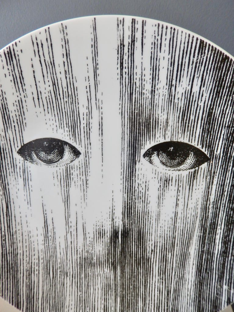 An evocative porcelain plate by Piero Fornasetti (1913-1988) of Lina Cavalieri, the artist's muse, perhaps shown behind a mask or screen. This powerful image suggests that Fornasetti is alluding to the