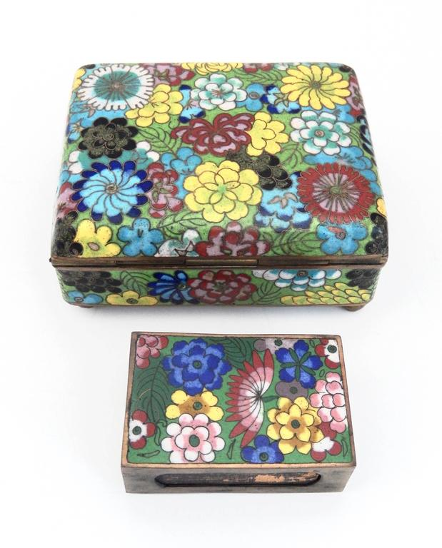 A multicolored, lidded box and match holder with an enameled floral pattern.