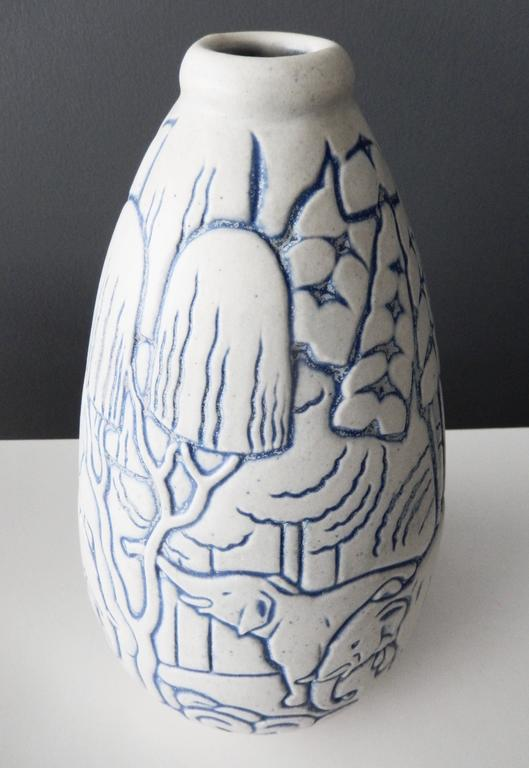 A tall, French Art Deco vase designed by Andre Legrand (1902-1947) for Les Freres Mougin (Joseph and Pierre Mougin), Nancy, France. As is typical of Mougin ceramics, the vase depicts stylized nature elephants in a natural, idealized setting of trees