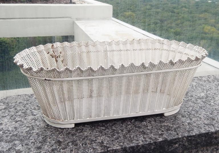 A chic, perforated metal flower basket (jardiniere rigitulle) by the modernist French designer Mathieu Matégot (1910-2001). Mategot pioneered the use of perforated sheet metal and lacquered steel in his furniture and decorative objects. Original