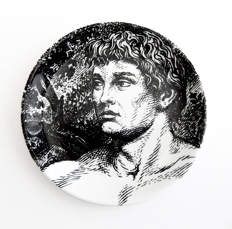 A complete set of eight Fornasetti coasters depicting a reclining, biblical Adam. Fornasetti has created a fascinating, interactive ceramic jigsaw puzzle of the figure of Adam to be arranged by the viewer. This set is in excellent condition and