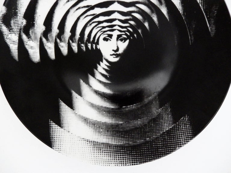 A porcelain plate with a mesmerizing Op Art design by Piero Fornasetti (1913-1988). He depicts his muse, Lina Cavalieri, in a series of overlapping plates, creating the illusion of movement. Very strong graphic design. Marked: Rosenthal Germany.