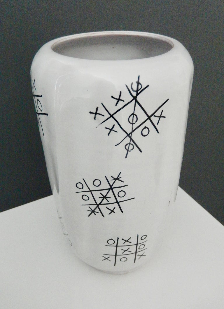 A scarce, faceted vase by Ed Langbein with a original design of several tic-tac-toe games, resembling graffiti. Since games shown are won equally by both players and some a draw, Langbein is depicting a fair game for both players. A wonderful,