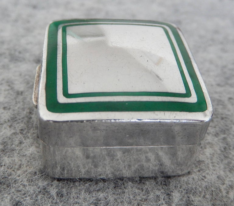 A petite 1970s sterling and green enamel pillbox by Cartier. The geometric design of a square within a square is a very attractive example of modern design from the period. C'est tres chic. Marked