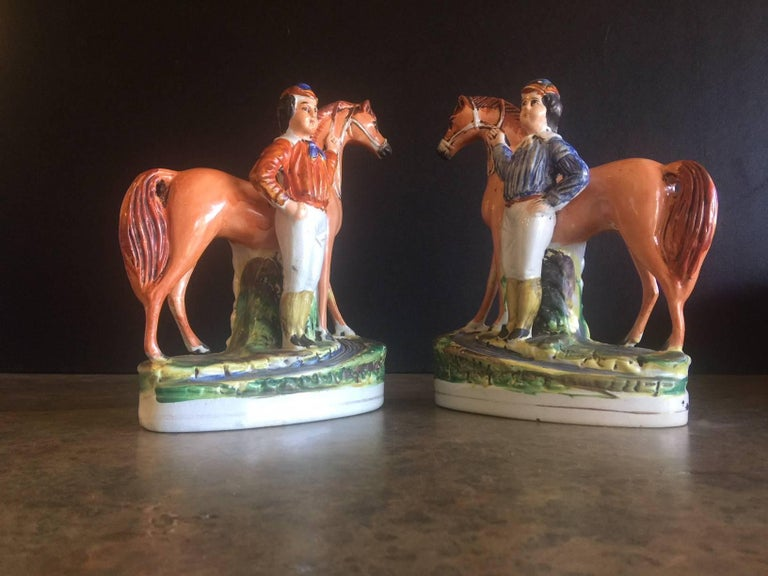 Excellent pair of English porcelain horse and rider/jockey figurines by Staffordshire, circa mid-19th century. The figurines are in very good antique condition with a very minor chip on one of the jockeys noses (please see pictures). The color is