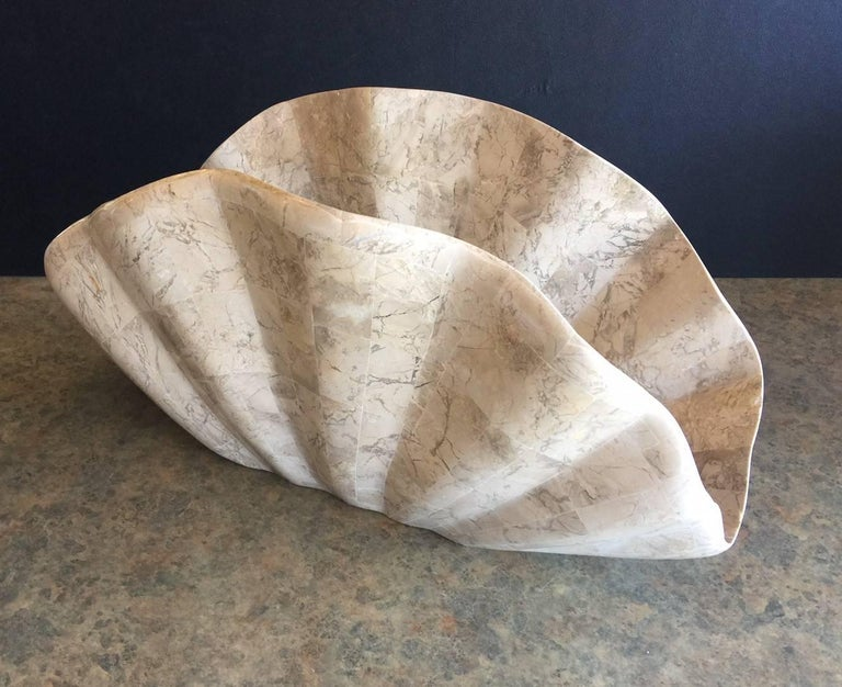 Unique magazine rack in the shape of a clam shell made of tessellated stone by Marquis of Beverly Hills, circa 1970s. The piece is composed of cream, white and tan colored tessellated inlaid fossil stone buffed to a elegant shine. Very heavy and