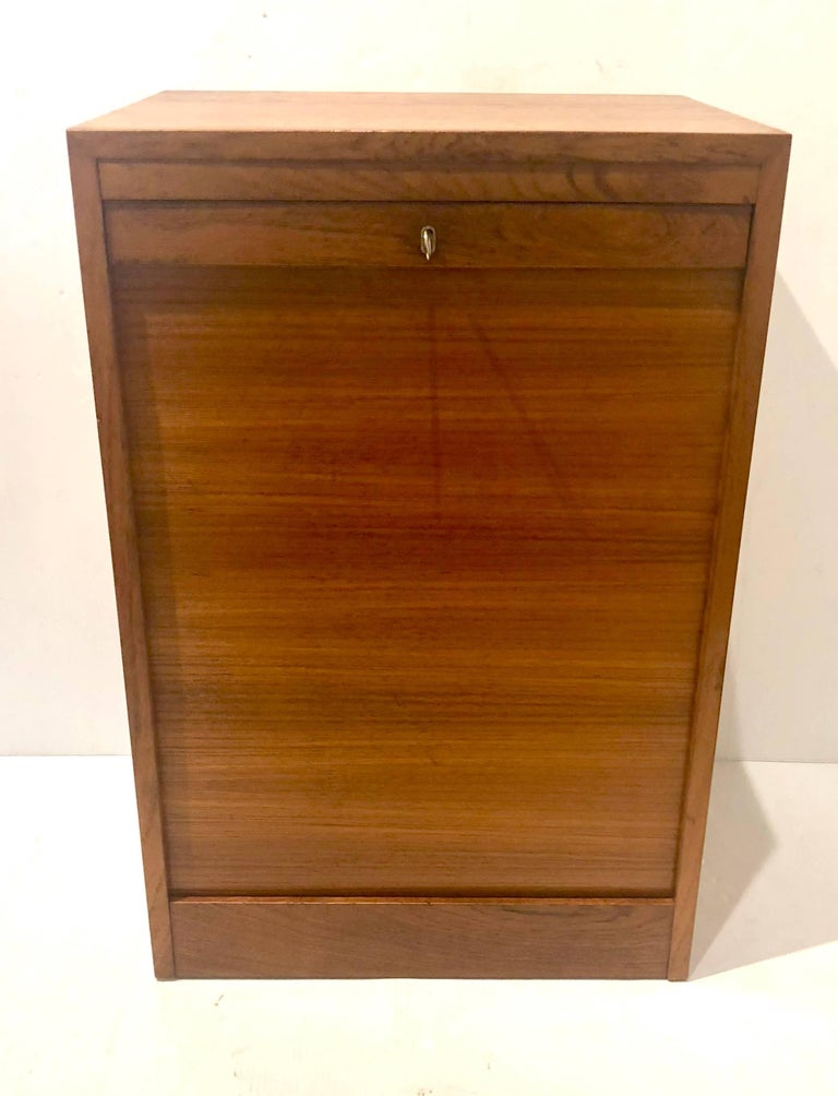 Versatile file cabinet or artist cabinet in original finish teak with lock key, and tambour door, drawers finish in birch wood, hard to find piece, each drawer. Measures: 12