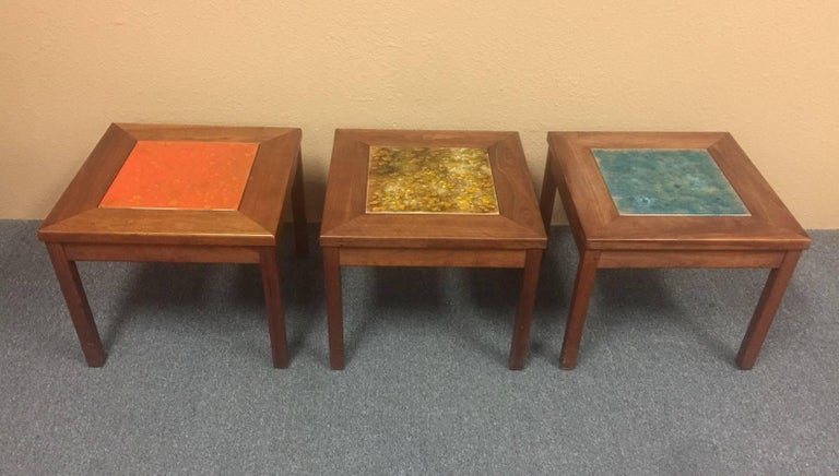 """Unique and rare set of three """"Constellation"""" end or side tables by John Keal for Brown Saltman, circa 1960s. The table legs and frames are walnut with a large enameled ceramic centre tile in the table top. The tables come in an orange/yellow,"""