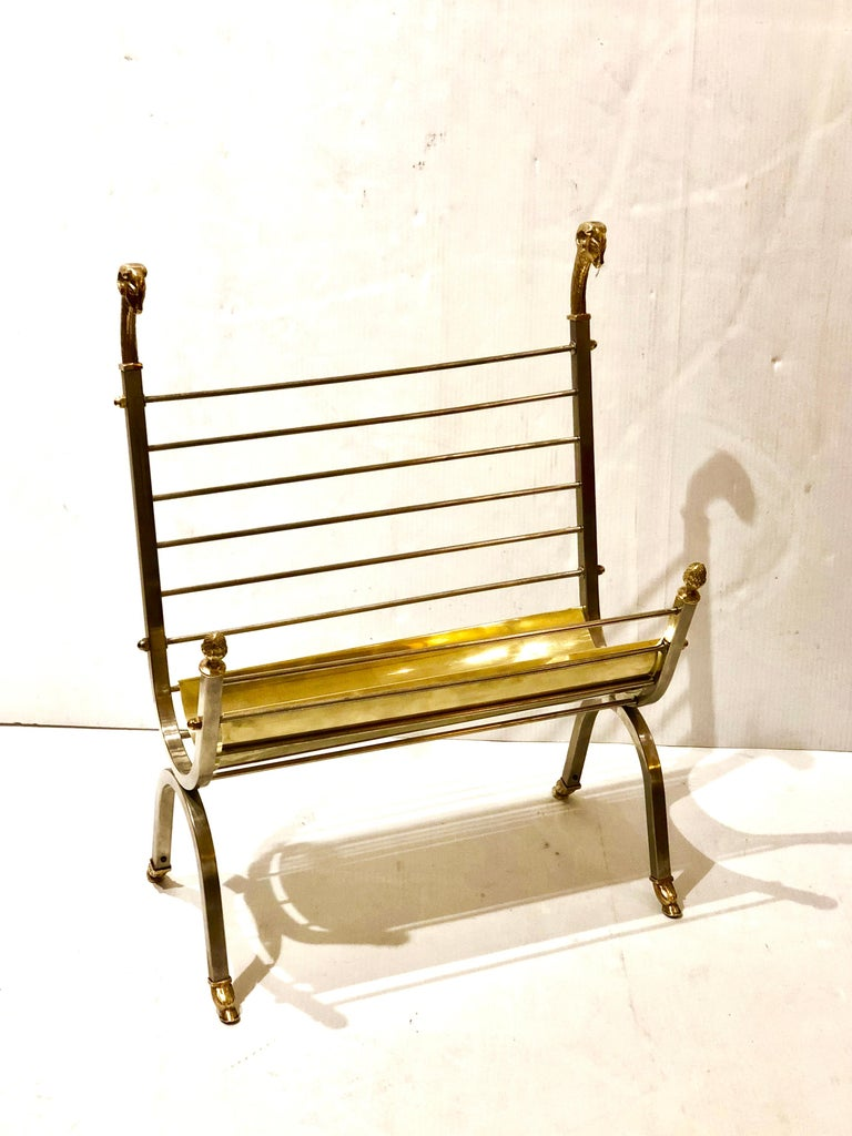 Tall magazine rack in brass and stainless, freshly polished with brass rams heads accents.