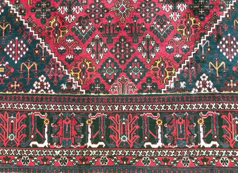 This Authentic Joshaghan rug is hand-knotted in Iran. The age of this rug is almost 50 years old. Colors found in this piece are burgundy, indigo blue, yellow and black. The size is 8 feet 3 inches by 11 feet 10 inches. The design has geometric