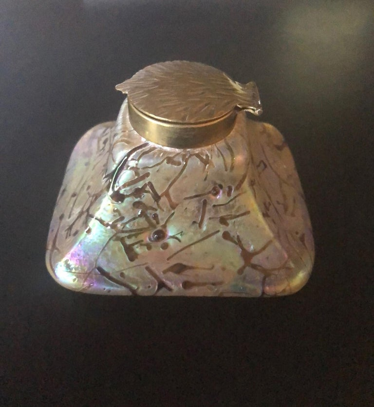 Stunning early Art Nouveau threaded iridescent art glass inkwell with insert by Loetz, circa 1900s. The piece features a gorgeous array of rainbow iridescence from pinks to blues to greens to browns. The inkwell is capped with a gorgeous brass leaf