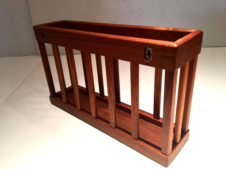 Nice craftsmanship on this solid teak magazine rack, circa 1970s it can be used on the floor, or wall-mounted has two holes where it can be hooked, its been freshly restored.