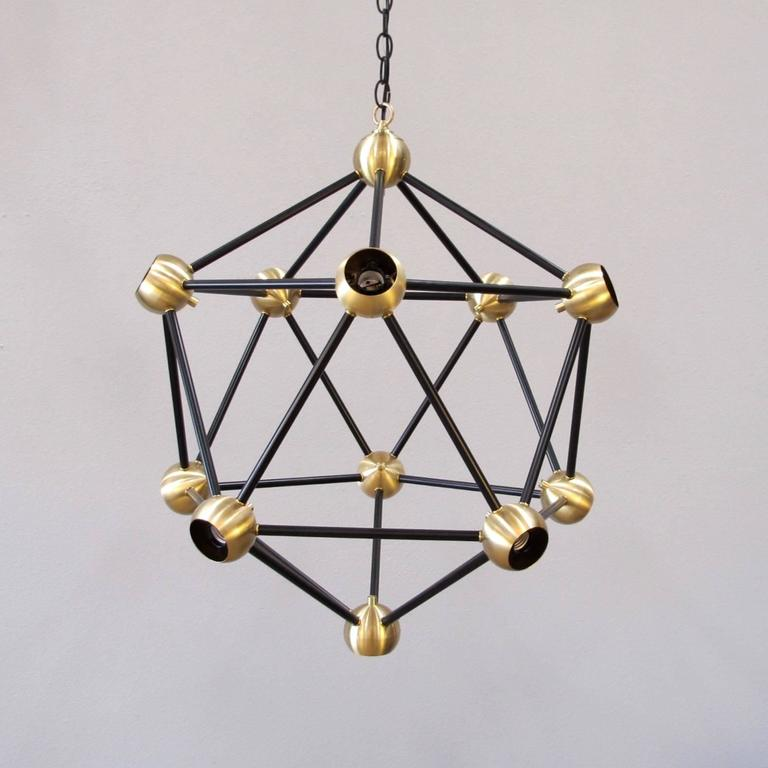 Striking black and brass large pendant light. 11 lights, medium base sockets up to 40 watts/socket. Works great with large round light bulbs for a dramatic effect. Bulbs not included. Can be hung on rod or chain. Custom sizes and finishes available.