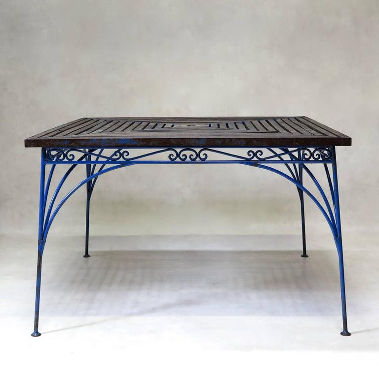 Elegant and unusual outdoor/garden dining set, comprising a large square table and four large armchairs. The structure is made of hand-wrought iron, and the table top and chair seats are made of wooden slats.  There is a hole in the table centre