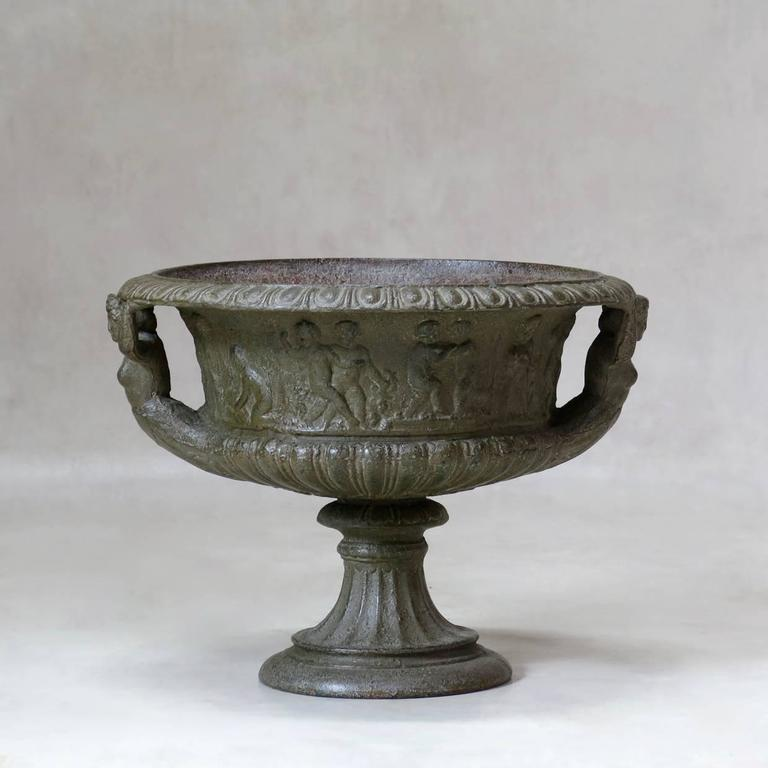 Classical pair of 19th century cast iron urns or planters with a dark silver/grey patina.