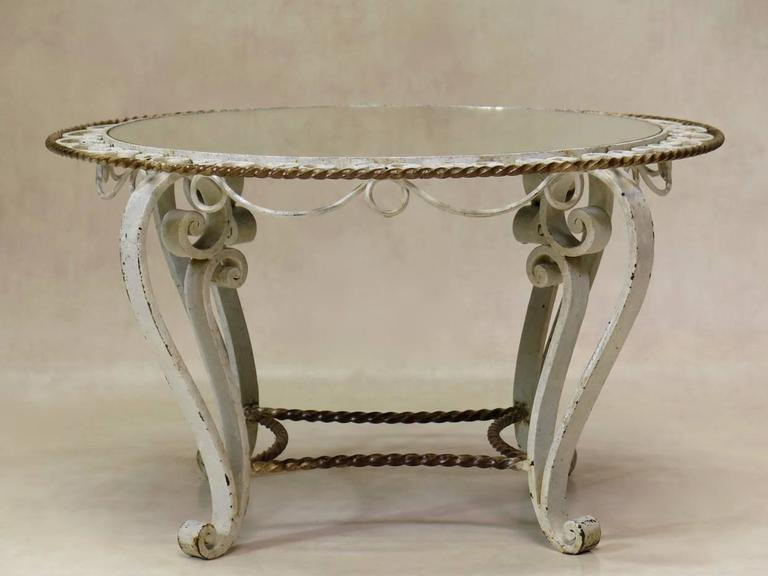 Charming French Art Deco coffee or side table from the 1940s with a heavy yet dainty wrought iron base, with original cream and gold paint. The mirrored top is set in a decorated surround.