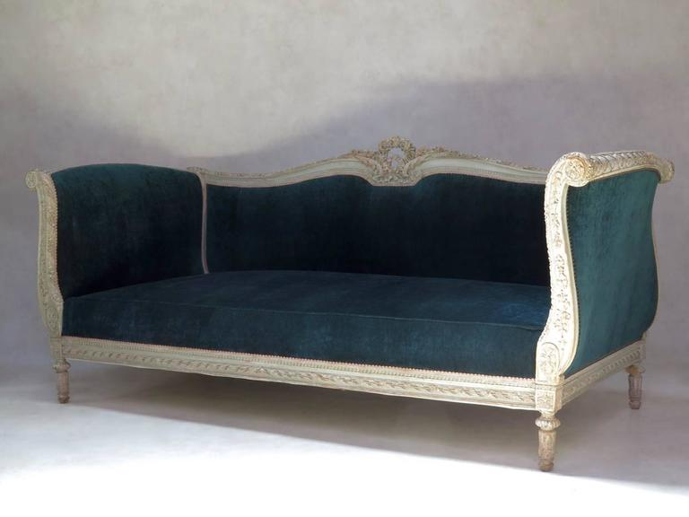 Large and deep Louis XVI style sofa. The carved wooden structure is elegantly decorated with motifs typical of the style (ribbon, flower and acanthus leaf detail on the back crest; rosettes; beading; fluted legs...) and retains its original