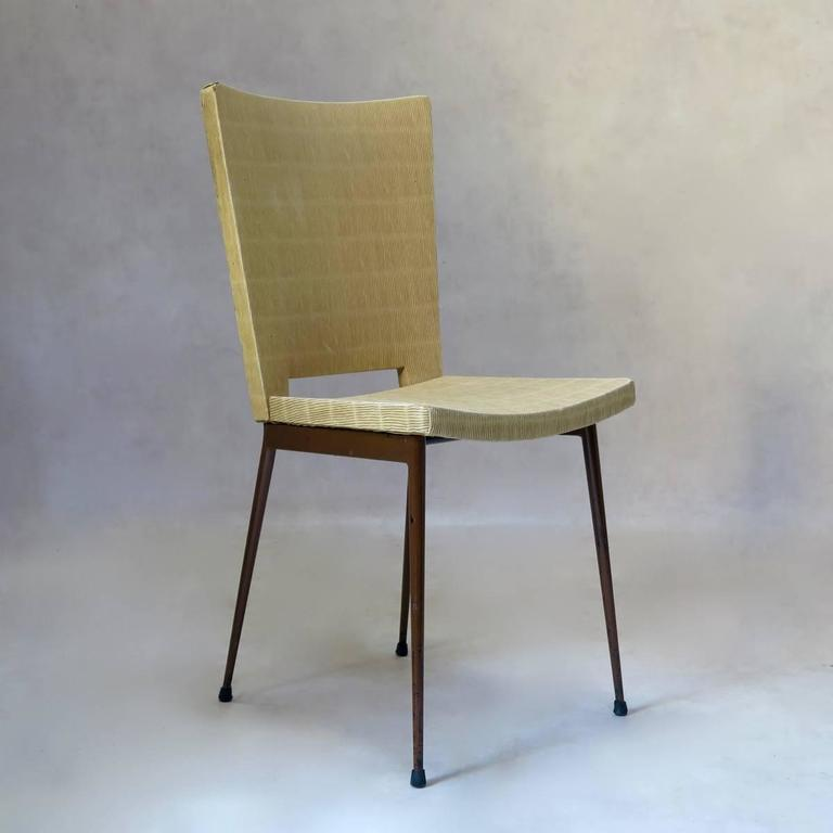 Fantastic set of four dining chairs with splayed and tapering iron legs, with brown finish. Curved seats, and cutout detail at the base of the backs. The seats and backs are upholstered in original faux-rush plastic, very typical of Colette Gueden.