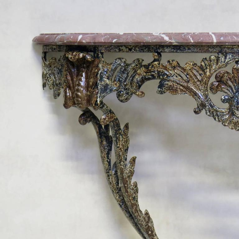 Lovely demilune console table with a forged iron base in the Rocaille style, decorated with acanthus leaves and shell motif. The iron has a gorgeous patina. Original pink marble top.