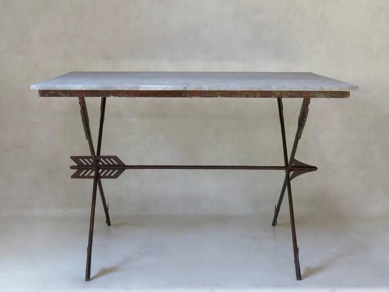 Chic and one-of-a-kind table with a stylized arrow iron base and original marble top.