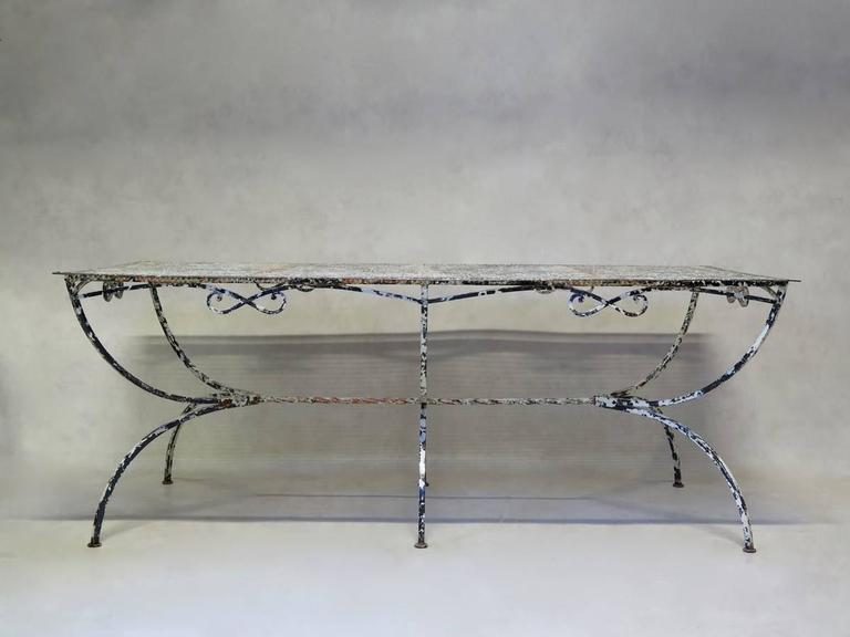 Large wrought iron, bow-motif painted garden or outdoor dining table. The top is made of cloverleaf-patterned sheet metal. Curule-style base, with a bow-motif apron and twisted iron stretcher.