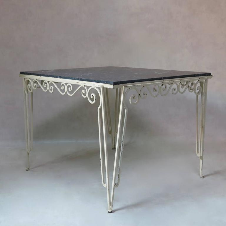 An unusual, large and almost square table with a painted wrought iron base and a mottled black and white stone top.