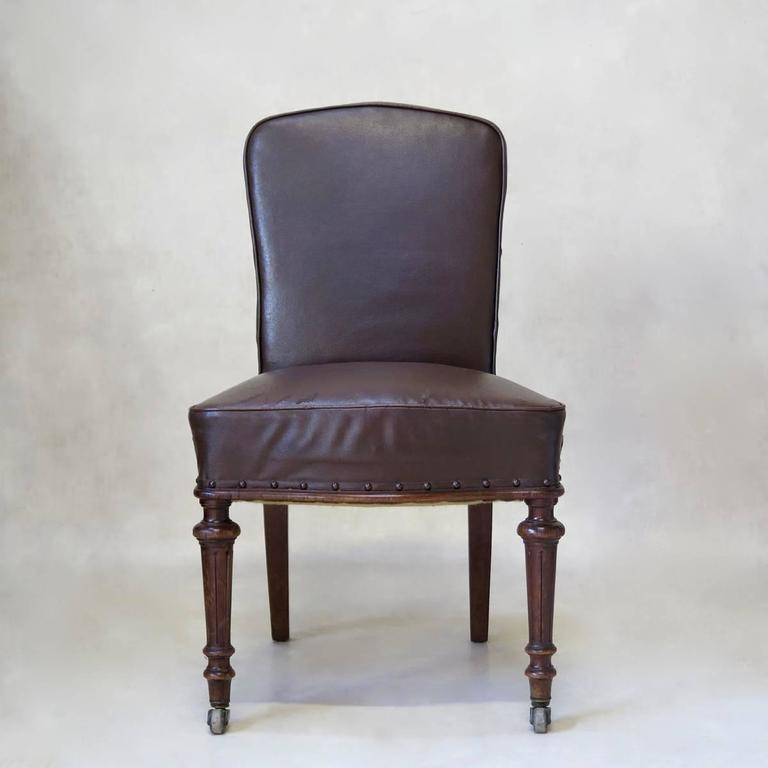 Handsome 19th century desk chair raised on turned front legs, on original brass casters and saber back legs. Upholstered in original antique faux-leather, with nail-head trim.