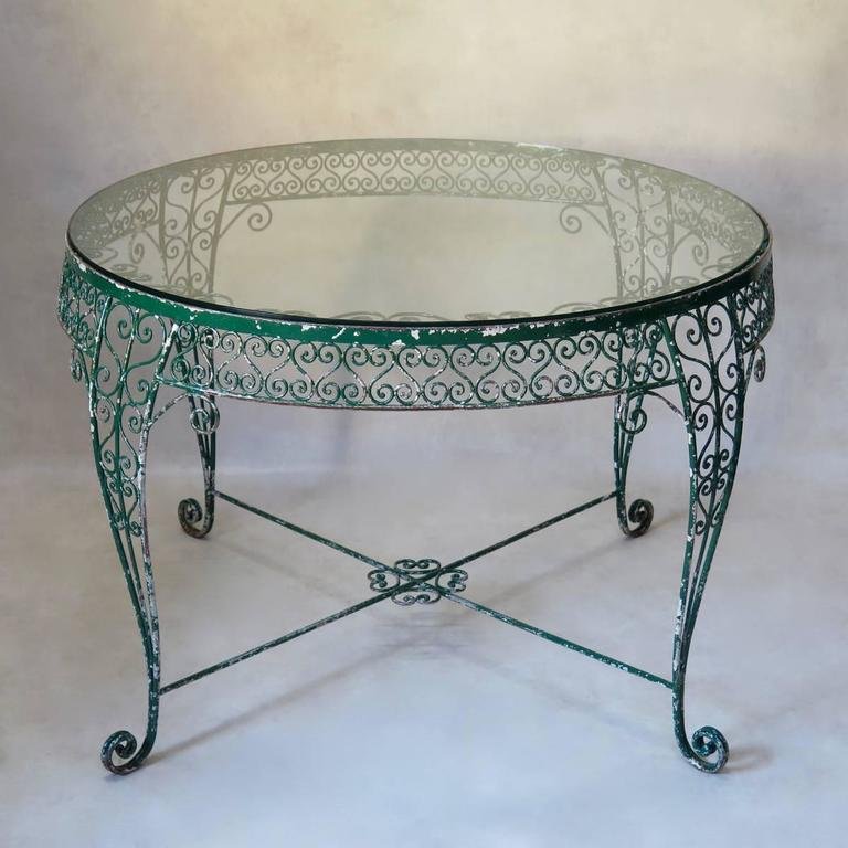 Very elegant and unusual garden set comprising a large, round table and three chairs. Made of wrought iron, with original green paint. The table has a very intricate arabesque motif, and is raised on cabriole legs. The thick glass top slots into the
