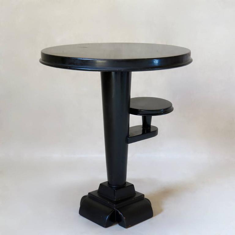 Elegant little side table with a smooth, shiny, black lacquered finish. Conical stem, tapering down to an unusual, stacked foot. Additional little shelf mid-way up the stem. Delicate and refined.
