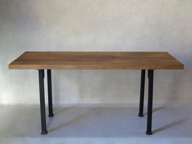 Very chic and understated table with a heavy, solid iron base which fixes to the solid oak top by means of screws. The wood has a warm, golden hue. The square legs flare out slightly at the base, subtly lending aplomb to the overall look. A refined