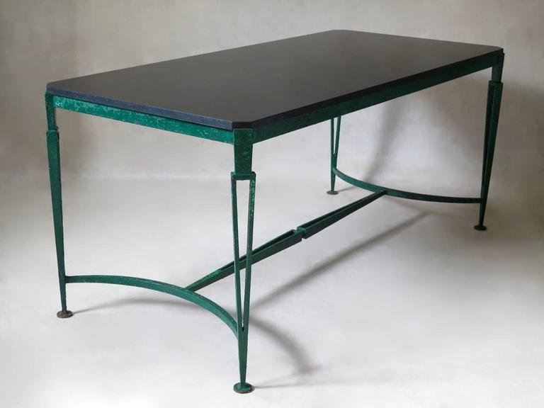 Very handsome large Art Deco table, with a wrought iron base of neoclassical inspiration. Tasteful design with minimalist lines. The black granite top has canted corners. Raised on slender, tapering legs. The open ironwork of the legs and stretcher