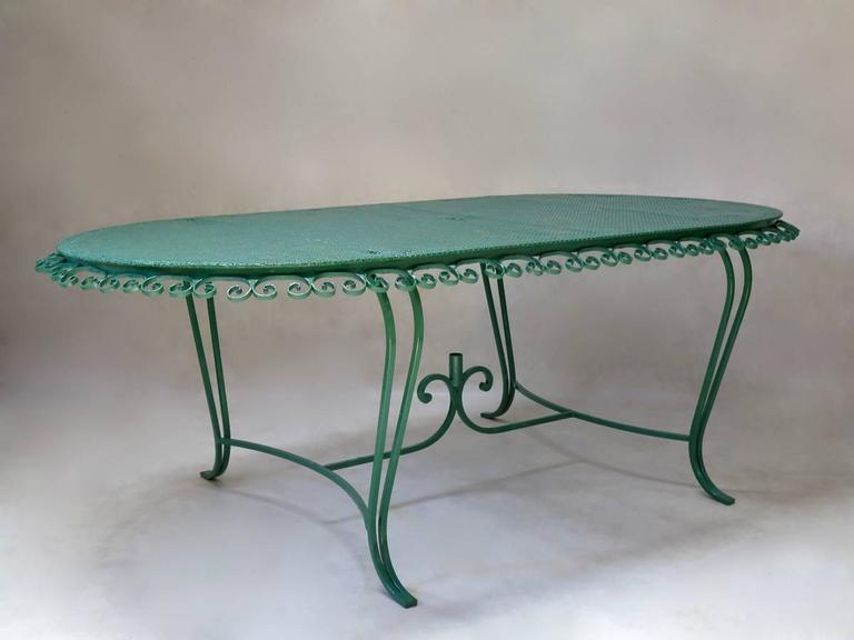 Charming Mid-Century outdoor dining set comprising a table and eight chairs, made of wrought iron, with perforated cloverleaf patterned iron table-top and chair seats.  The table has a characteristic clover-leaf patterned top, with lovely