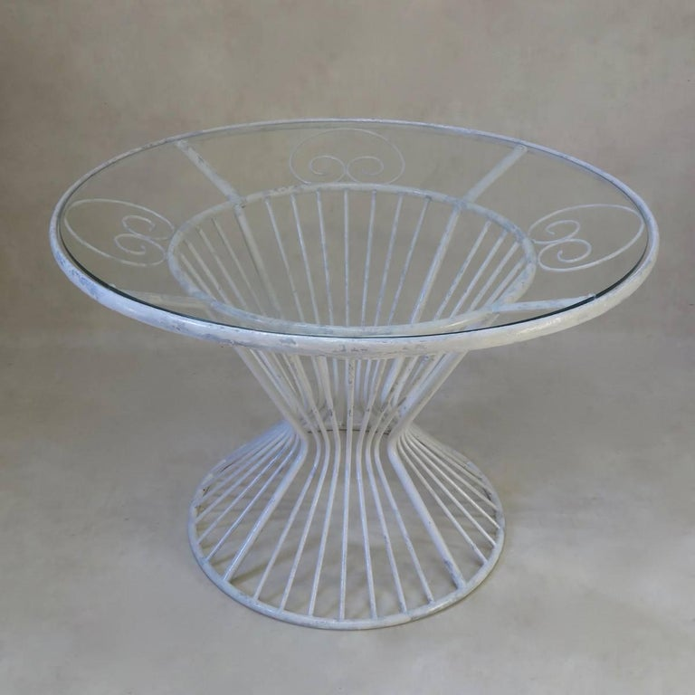 A French, circa midcentury round dining table of nice design, made of painted iron, and fitted with a safety glass top.