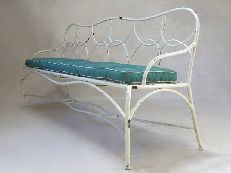 Pretty and unusual painted iron garden bench, with original green cotton canvas cushions. Sprung seat base.