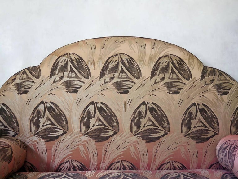 Lovely and unusual Art Deco settee, with a scalloped back and arched armrests, raised on short, tapering block feet with dentil frieze running around the base. Original and charming albeit rather faded and worn pink silk upholstery.