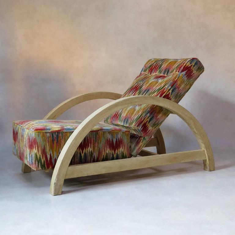 Large and comfortable Art Deco period armchair of unusual design. The structure presents a large and streamlined arc shape and is of brushed oak. The seat and back have been newly upholstered in vintage ikat-like velvet fabric. The chair is