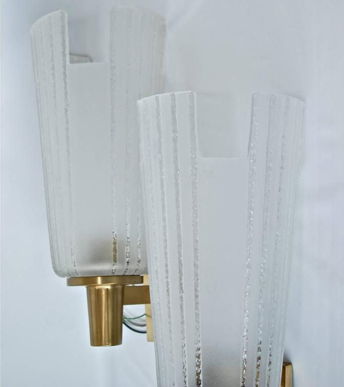 A pair of large Swedish Art Deco wall lights, circa 1940. Attributed to Orrefors. Brass, striped sandblasted glass shades. Measures: Height 50 cm (20