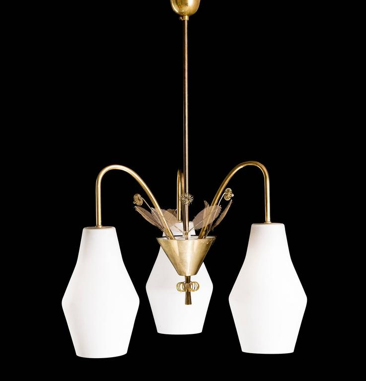 A pair of chandeliers designed by Paavo Tynell, model K1-9/L, Idman, Finland, 1950s. Marked by manufacturer. Existing wiring, we do not guaranty functionality, rewiring available upon request.