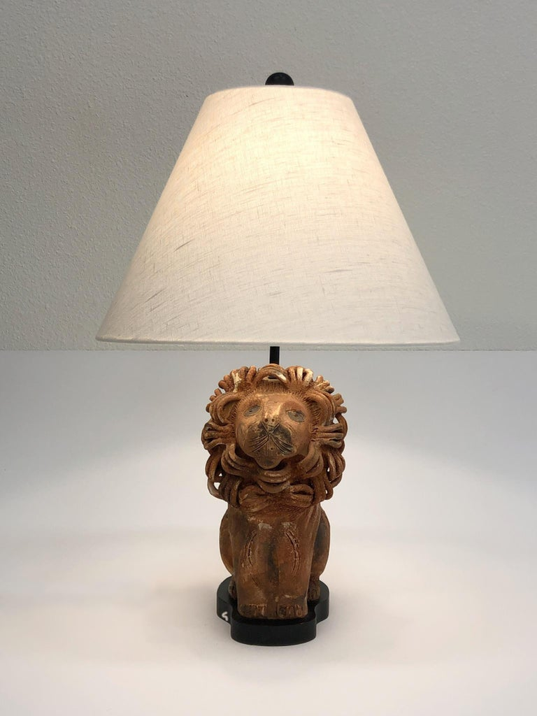 A rare Italian ceramic lion table lamp by renowned Italian ceramicist Aldo Londi for Bitossi. The lamp has a light brow volcanic glazed and black lacquer. Newly rewired and new vanilla linen shade. 