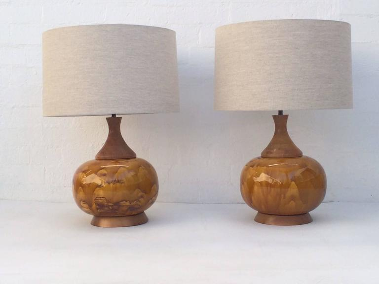 Pair of large-scale drip glazed ceramic lamps with walnut bases.  These lamps are absolutely stunning! Newly re-wired with new brass hardware. New off-white linen shades,  circa 1960s.