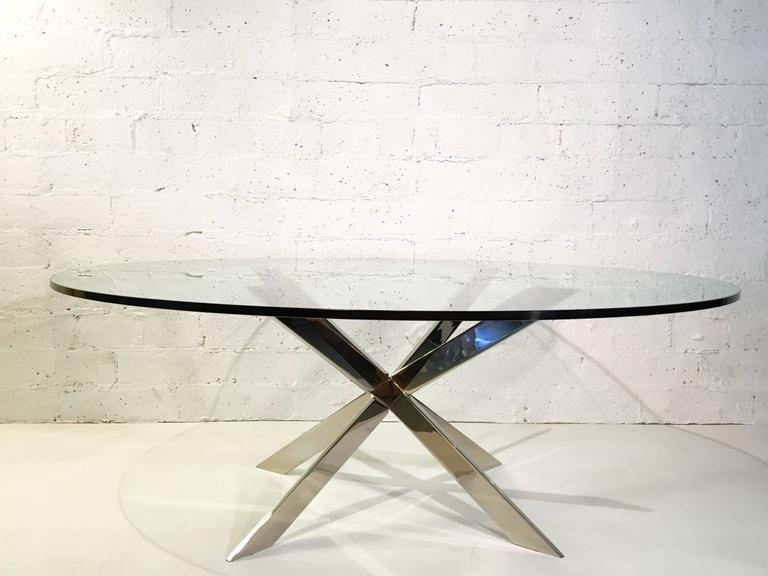 An elegant nickel X-base and glass cocktail table by Leon Rosen for Pace Collection. The base is a solid steel base, that has been newly nickel-plated and new 1/2