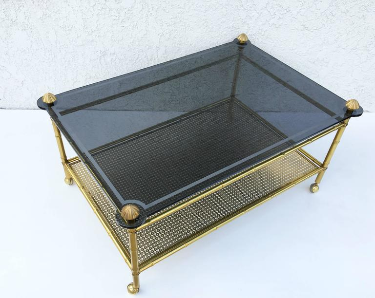 A glamorous 1960s French two-tiered brass faux bamboo and smoked glass top with a acidic edge design on casters. 