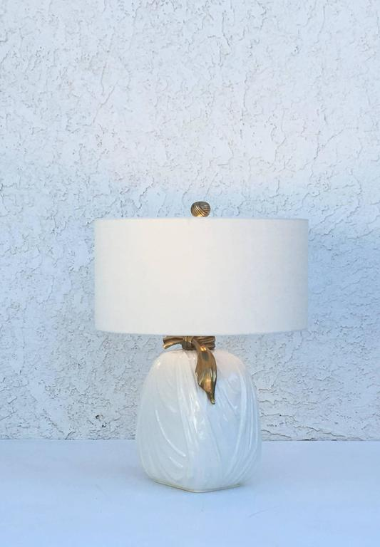 Pair of 1982 glazed ceramic and brass table lamps by Chapman.  Newly rewired and new vanilla linen shades.  The lamps have original finials. One of the lamps have small dent on glazed see detail photos.   Overall dimensions 20