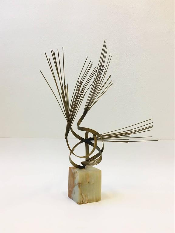 A original 1970s brass sculpture on a solid onyx base by Curtis Jeré.  Dimension: 33.25