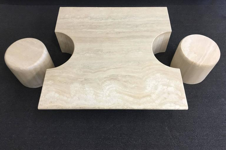 A spectacular three-piece Italian travertine cocktail table. The two drums can be used as side tables or ottoman. The finish is a satin finished. 