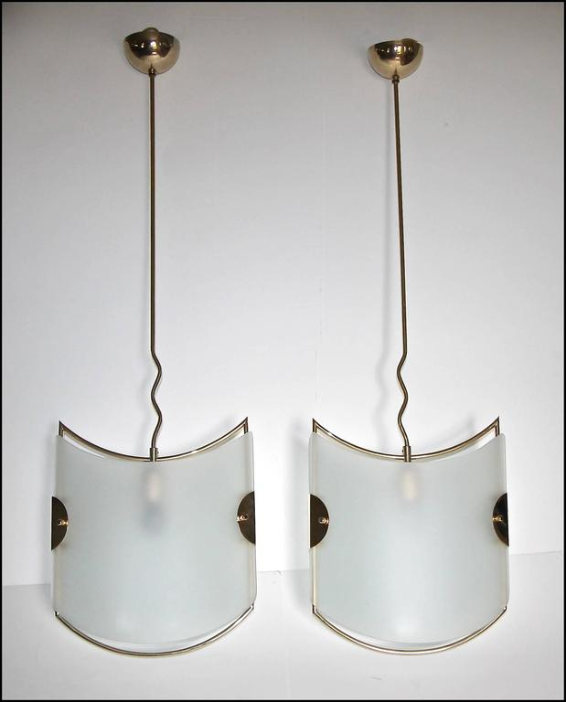 Pair of Italian pendant lights with frosted glass panels and brass finish frames. The modern style is very much in the manner of Gio Ponti for Fontana Arte. In addition to using in an entry or hall, this pair would look perfect over a kitchen or bar