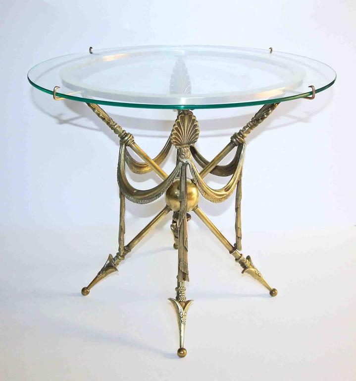 A brass side or occasional table with arrow and draped swag motif in the French Empire or Directoire style. New glass top is held to the circular brass top of table with attached arms.